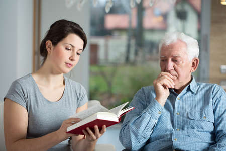 Young attractive caregiver reading the book to aged man Stock Photo