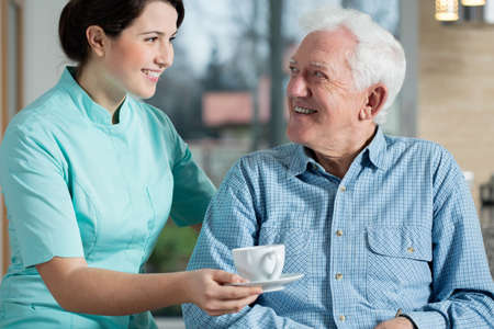 an elderly person: Young pretty nurse serving the cup of coffee to elderly smiling man