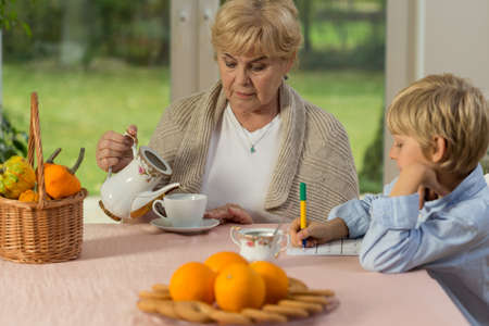 schoolwork: Little boy and his granny drinking tea during schoolwork