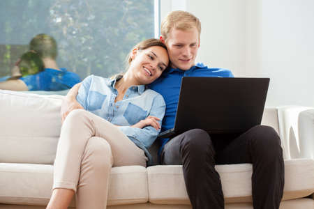 out of focus: A happy couple smiling when on their laptop on a sofa Stock Photo