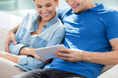 chilling out: A smiling man and woman sitting with a tablet
