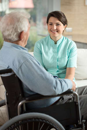 color therapist: Young pretty nurse and elderly patient on the wheelchair Stock Photo