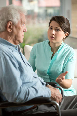 color therapist: Young worried nurse talking with with older man Stock Photo