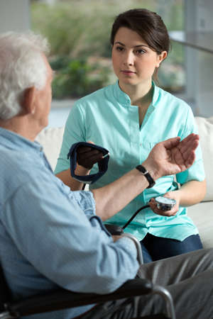 color therapist: Young pretty nurse checking the older mans blood pressure Stock Photo