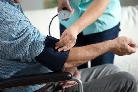 color therapist: Close-up of assessment elderly patients blood pressure Stock Photo