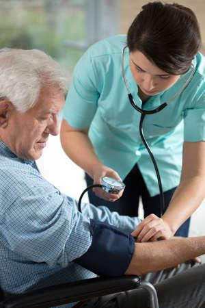 pielęgniarki: Młoda atrakcyjna pielęgniarka kontroli nadciśnienia tętniczego mężczyzny w podeszłym wieku