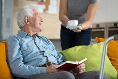 Elderly happy man reading the book and his tea time Stock Photo