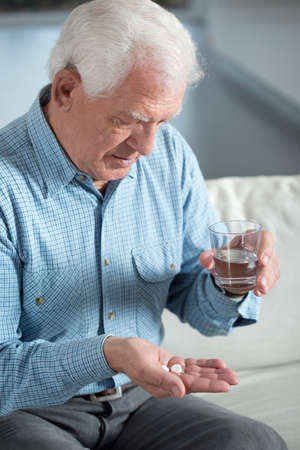 Elderly sick man taking the pills