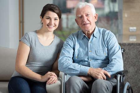 Jonge mooie vrouwelijke verzorger en oudere man op een rolstoel