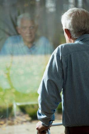 reflexion: Hombre débil mayor que mira a través de la ventana del hospital