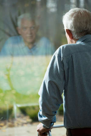 Elderly weak man looking through the hospital window