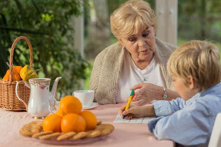 schoolwork: Lovely elderly grandmother helping little boy with his schoolwork