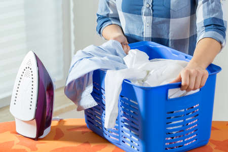 laundry room: Young woman holding basket full of clean laundry