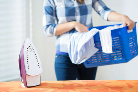 Photo of young woman bringing the clean laundry to iron Stock Photo