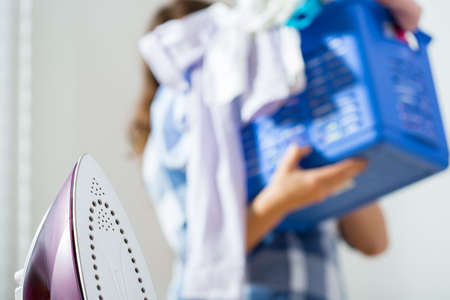laundry room: Photo of woman in the background holding the laundry basket Stock Photo