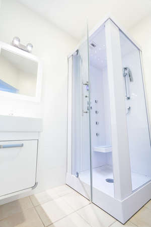 Bright white bathroom with a shower, vertical photo