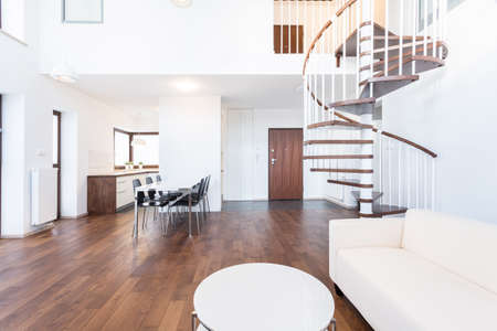 Big modern lounge with wooden spiral stairs photo
