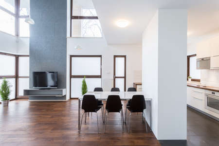 Big white table in spacious lounge with wooden floor