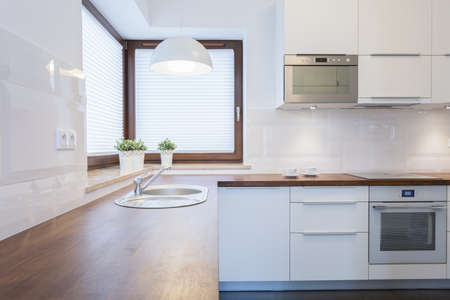 Contemporary clean kitchen with wooden wheat Imagens