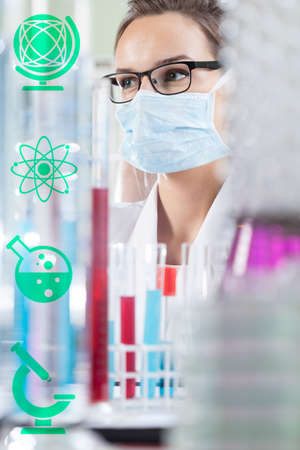 experimenting: Female chemist in laboratory and chemistry icons