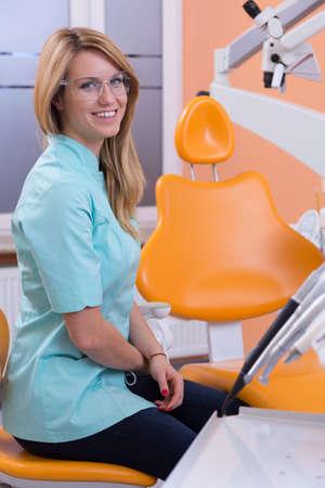 stool: Attractive female dentist sitting on dental stool