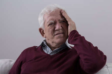 cephalgia: Senior man with headache sitting on the sofa