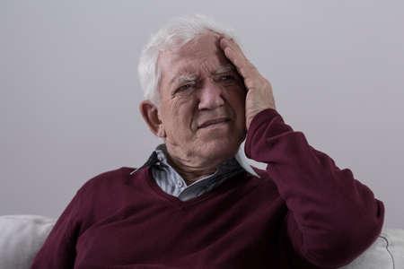 cephalgia: Senior man with headache sitting on the sofa