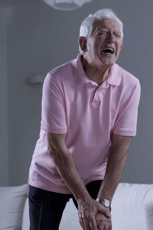 arthritis: Retired man suffering for terrible pain of the knee Stock Photo