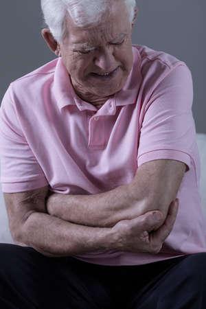 受傷後痛みを伴う肘を持つ年配の男性