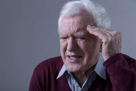Portrait of elderly man having terrible headache photo