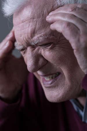 Close-up of elder man suffering for migraine photo