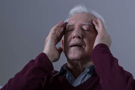 Senior man with headache touching his temples photo