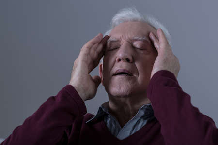 seniors suffering painful illness: Senior man with headache touching his temples Stock Photo