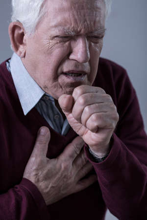 tosiendo: Un más viejo hombre que tiene dolor en el pecho y tos