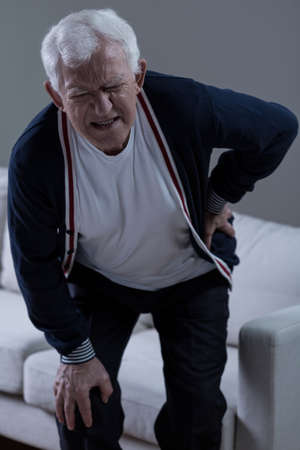 Senior man suffering for terrible pain of lower back Standard-Bild