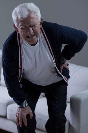 de rodillas: Hombre mayor sufrimiento para un terrible dolor de espalda baja