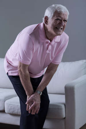 arthritis knee: Vertical view of pensioner having knee arthritis Stock Photo