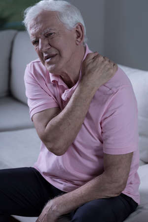 senior man on a neck pain: Senior with pain of the shoulder sitting on the sofa