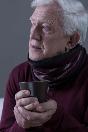 grippe: Ill senior man wearing scarf and holding cup of tea