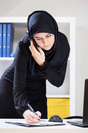 office notes: Vertical view of female muslim at work