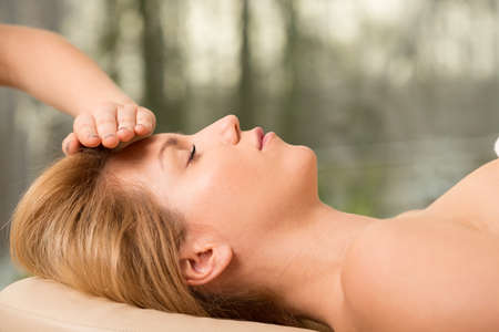 bioenergy therapy: Young attractive woman relaxing during head massage