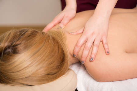 Young attractive woman having her back massaged photo