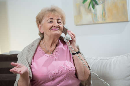 Portrait of elderly woman talking on stationary telephone 版權商用圖片
