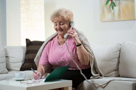 Zittend op de bank en praten over vaste telefoon Stockfoto