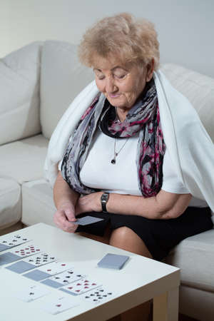 Active elder woman playing solitaire at home Stock Photo