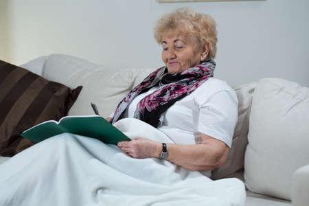Portrait of senior woman doing crossword puzzle photo