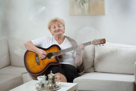 Ltere Frau, die allein zu Hause und spielt Gitarre Standard-Bild - 35821808