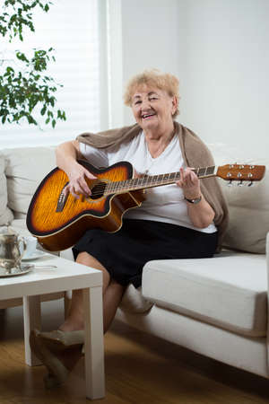 old: Portrait of elderly woman playing the guitar