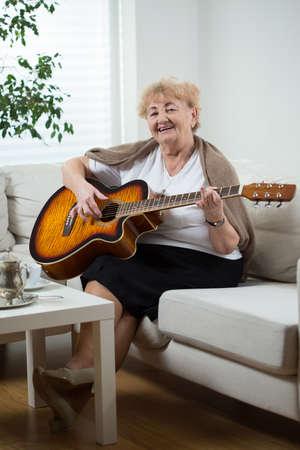 vestidos antiguos: Retrato de la mujer mayor que toca la guitarra Foto de archivo