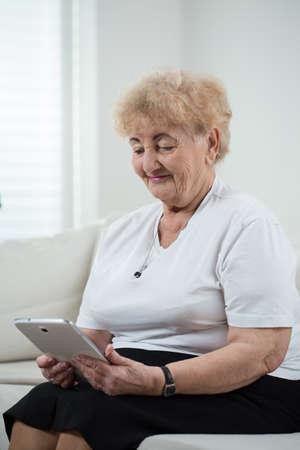 Vertical view of modern grandma using tablet photo